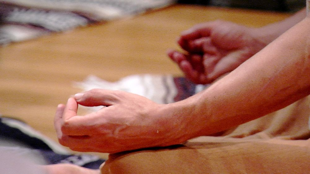 hands clasped in gyan mudra during yoga meditation