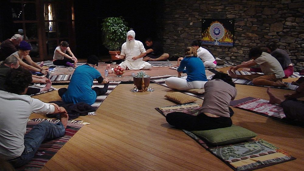 turban teaching forward-fold during yoga class to help students flower their hearts